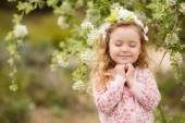 Portrait of little girl outdoors in a lush garden. — Stock Photo