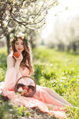Pregnant woman in the spring garden with a basket of ripe apples. — Stock Photo