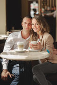 Happy couple drinking coffee in an urban café. — Stock Photo