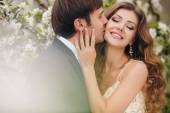The groom kisses the bride in the flowered Park in the spring. — Stock Photo