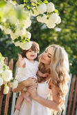 Portrait of happy woman with a small daughter in the village in the spring — Stockfoto