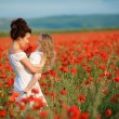 Mother with her little daughter in her arms in a field of blooming poppies. — Stock Photo #76620863