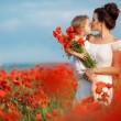 Mother with her little daughter in her arms in a field of blooming poppies. — Stock Photo #76620871