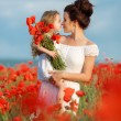Mother with her little daughter in her arms in a field of blooming poppies. — Stock Photo #76620885