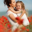 Mother with her little daughter in her arms in a field of blooming poppies. — Stock Photo #76620887