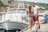 Young couple on a walk in the Harbor with a white Labrador — Stock Photo