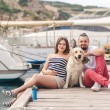 Young couple on a walk in the Harbor with a white Labrador — Stock fotografie #77865840