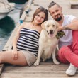 Young couple on a walk in the Harbor with a white Labrador — Stockfoto #77865848