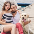 Young couple on a walk in the Harbor with a white Labrador — Stock Photo #77865904