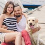 Jeune couple sur une promenade dans le port de plaisance avec un Labrador blanc — Photo #77865904