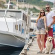 Young couple on a walk in the Harbor with a white Labrador — Stock fotografie #77865978