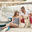 Young couple on a walk in the Harbor with a white Labrador — Stockfoto #77866008