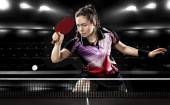 Young pretty sporty girl playing table tennis on black background. Action shot. — Stock Photo