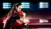 Young pretty sporty girl playing table tennis on black background with lights — Stock Photo