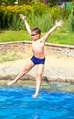 Boy jumping into a swimming pool — Stock Photo