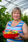 Woman with vegetables in a greenhouse — Stock Photo
