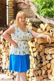 Portrait of a women near woodpile — Stock Photo