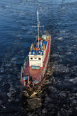 Small ship floating in the water among the ice floes — Stock Photo