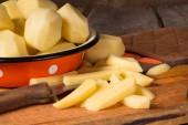 Raw potatoes in a vintage enamel bowl  — Stock Photo