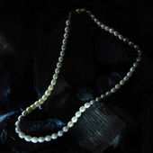 Pearl necklace on black carbon — Stock Photo
