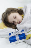 Little girl sleeping in bed with gift — Stock Photo