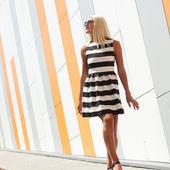 Fashion girl on background of orange wall — Stockfoto
