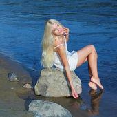 Sweet girl sitting on rock by sea — Stockfoto