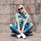 Girl in jacket sitting on a skateboard — Stock Photo