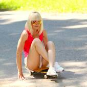 Mädchen reitet auf skateboard sitzt — Stockfoto