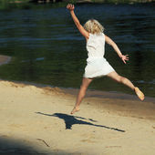 Girl happily jumping on the beach — Stockfoto