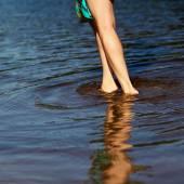 Girl walks through the shallow water — Stockfoto