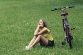 Young girl and bike on green lawn — Stock Photo