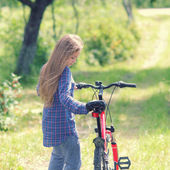 Teenager girl with bicycle in countryside — Stock Photo