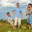 Family of four having fun on top of hill — Stock Photo #52594731