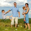 Family of four having fun on top of hill — Stock Photo #52594733
