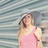 Girl in a hat against metal wall — Stockfoto
