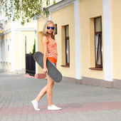 Woman with skateboard on city street — Stock Photo