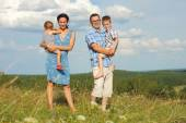 Family of four standing on a mountain — Stockfoto