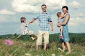 Family of four having fun on top of hill — Stock Photo
