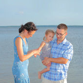 Young family having fun on the beach — Stock Photo