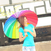Girl with rainbow umbrella on roof of house — Stockfoto