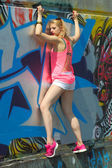 Trendy blonde climbs a wall with graffiti — Stock Photo