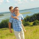 Father giving his son piggyback ride — Stock Photo #52621279