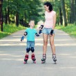 Mother and son learn roller skating — Stock Photo #55397175