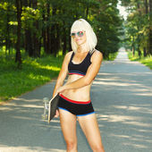 Athletic sporty girl with skateboard — Stock Photo