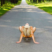 Jeune fille assise sur la planche à roulettes — Photo