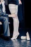 Girl in white stockings seduces man indoors — Stock Photo