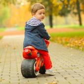 Young boy on toy motorcycle — Stok fotoğraf