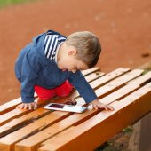 Boy with the tablet on bench — Stockfoto