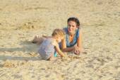 Mom with a baby girl playing on the beach — Стоковое фото